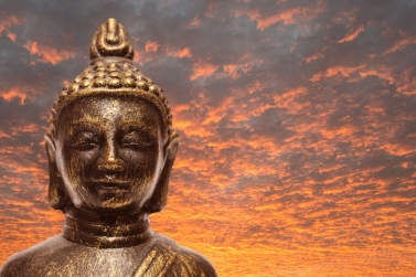 Buddha with orange clouds in the sunset